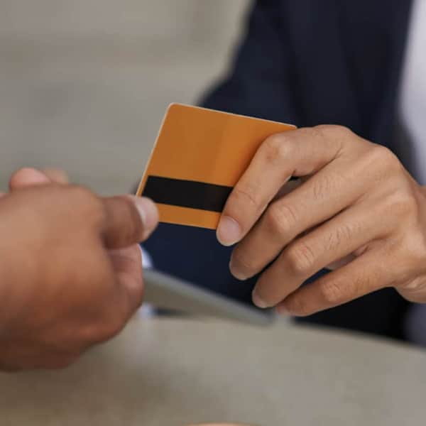 One person handing a PRO Club Rewards card to another person